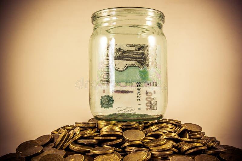 Heel wat muntstukken en een glaskruik stock afbeeldingen