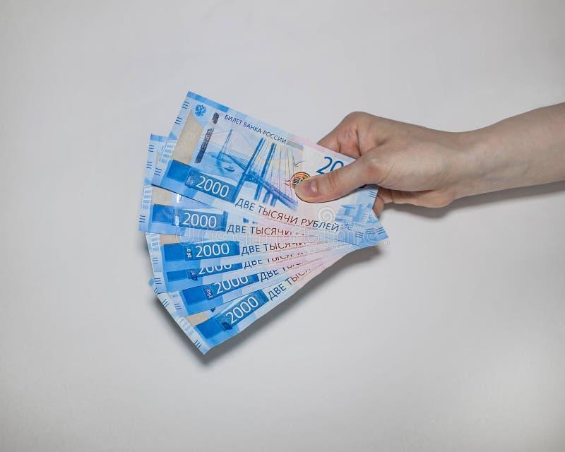 Heel wat nieuwe bankbiljetten houden twee duizend Russische roebels in hun hand royalty-vrije stock foto