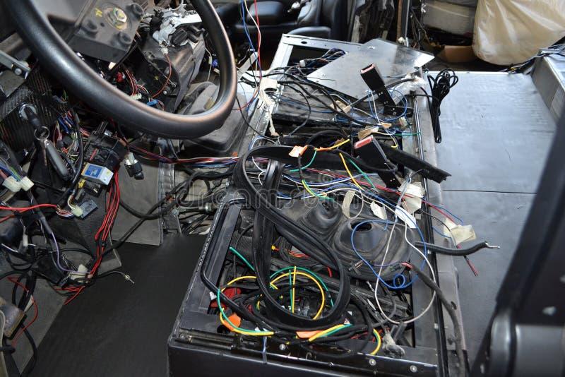 Heel wat rafel multicolored draden van de auto bedrading ligt in de cabine van ontmantelde auto met schakelaars en stoppen, een m royalty-vrije stock foto