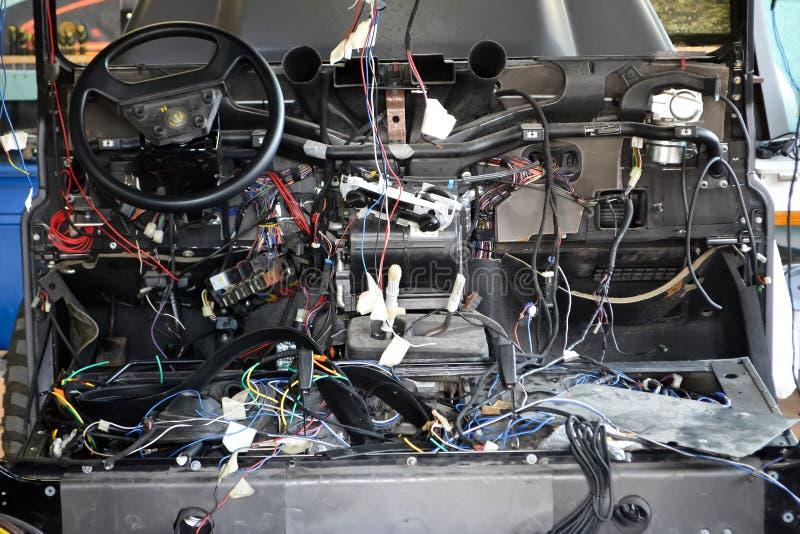 Heel wat rafel multicolored draden van de auto bedrading ligt in de cabine van ontmantelde auto met schakelaars en stoppen, een m royalty-vrije stock fotografie