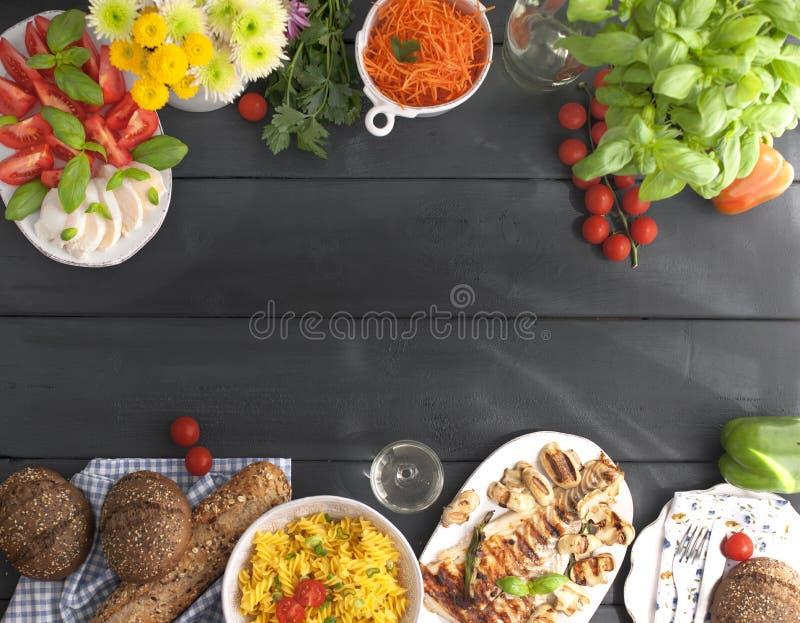 Heel wat verschillend voedsel op een zwarte lijst, hoogste mening Deegwaren, vers graangewassenbrood, geroosterde vissen, groente stock afbeelding