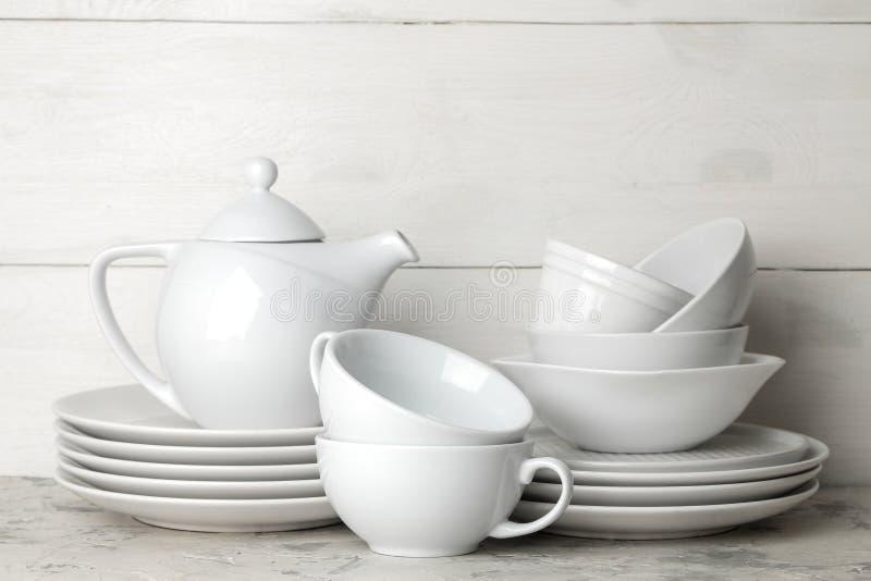 Heel wat verschillende schotels dinnerware op een lichte concrete achtergrond schotels voor het dienen van de lijst diverse plate royalty-vrije stock fotografie