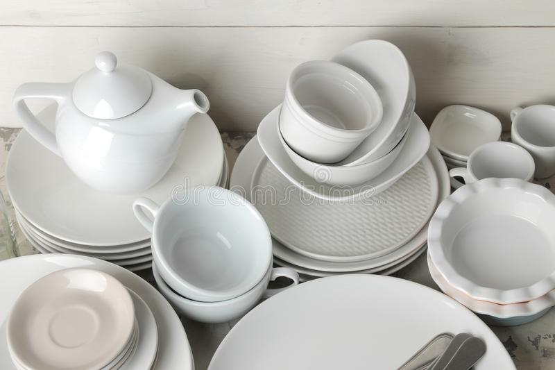 Heel wat verschillende schotels dinnerware op een lichte concrete achtergrond schotels voor het dienen van de lijst diverse plate stock foto