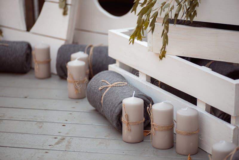 Heel wat witte geschilderde houten kooidozen, wat met decoratieve kaarsen, rolden dekens en binnenlandse installaties stock foto's
