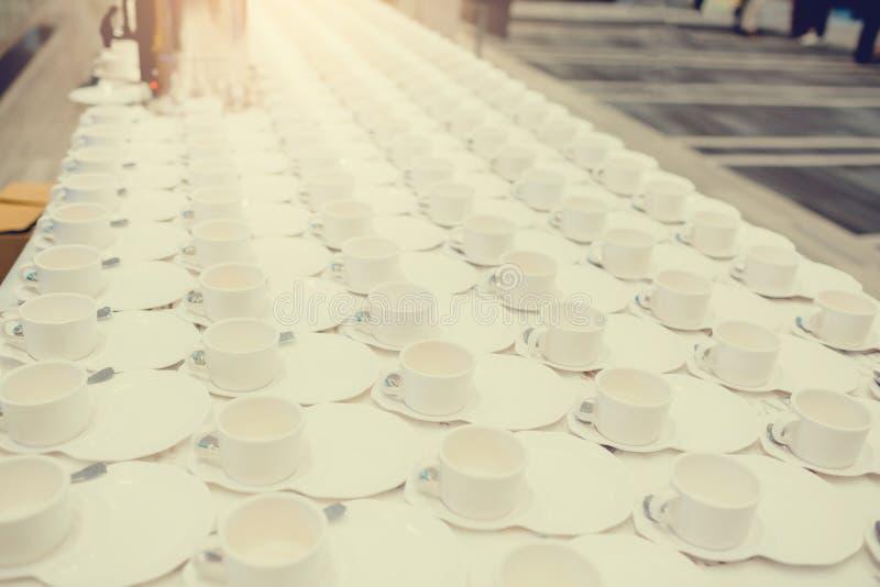 Heel wat witte koffiekoppen op witte lijst stock foto's