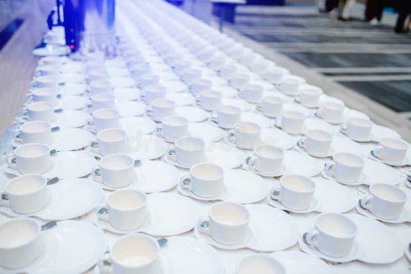 Heel wat witte koffiekoppen op witte lijst royalty-vrije stock afbeelding