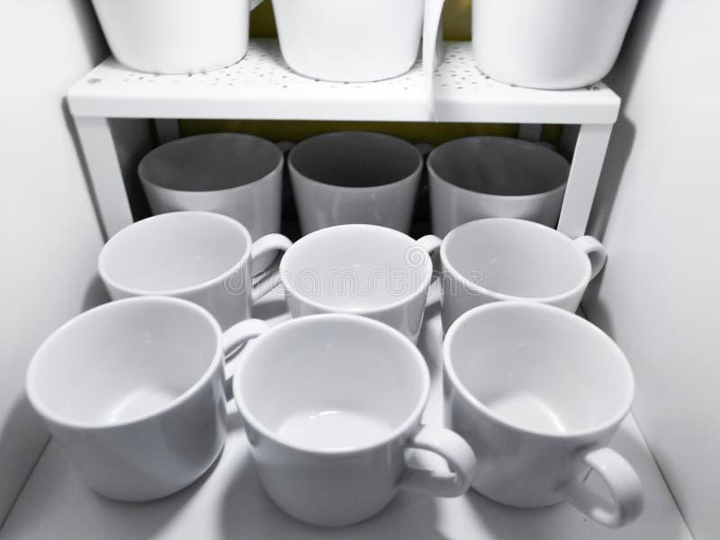 Heel wat witte koppen op de plank van huishoudenwerktuigen in een heldere keuken in een klassieke stijl stock foto's