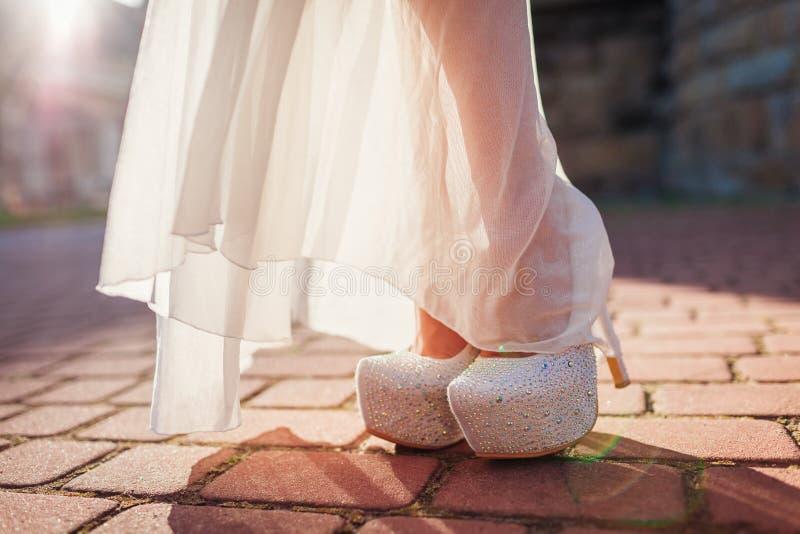 Heeled den bärande höjdpunkten för den stilfulla kvinnan skor och vitklänningen utomhus Skönhetmode arkivbild