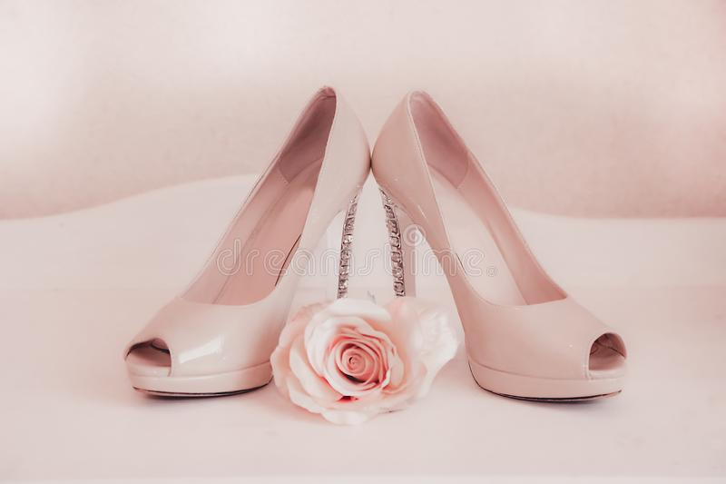 The heels of wedding shoes are decorated with precious stones. Wedding shoes pink high-heeled stand on the ladies ` table with a rosebud royalty free stock photo