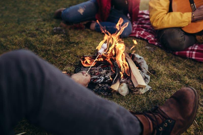 Heemst op een stok over een het kamperen brand wordt geroosterd die stock foto