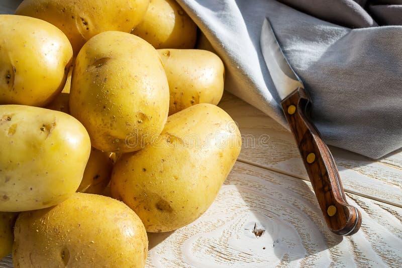 Heep van hele gele aardappelen en een pellingmes in het zonlicht op een witte houten tafel Groenten, vegetariër en gezond eten stock fotografie