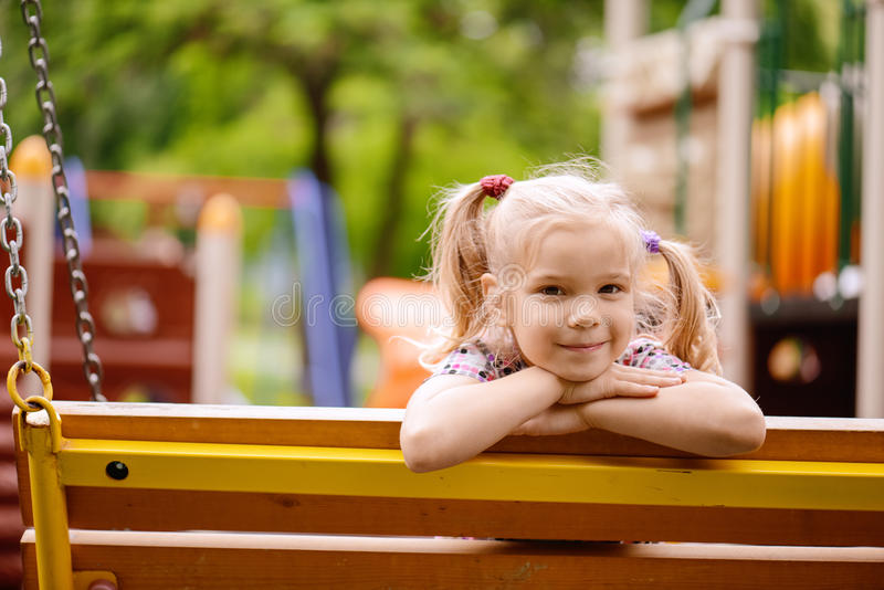 Heerful girl in dress. Little cheerful girl in dress on background of summer park royalty free stock images