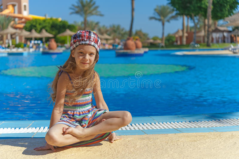 Heerful girl in striped vest. Little cheerful girl in lotus on background of Egyptian hotel stock photos