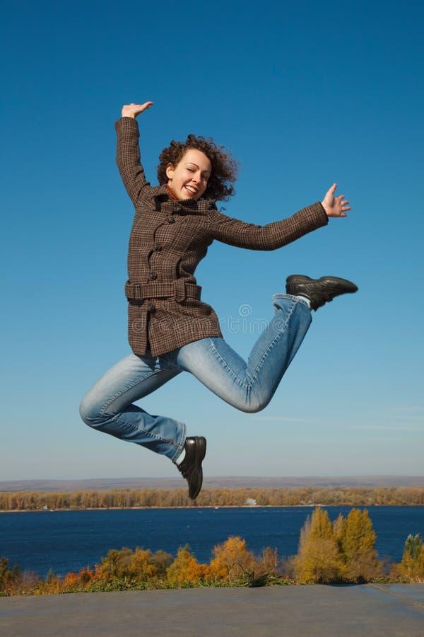 ?heerful meisje in sprong tegen donkerblauwe hemel stock fotografie