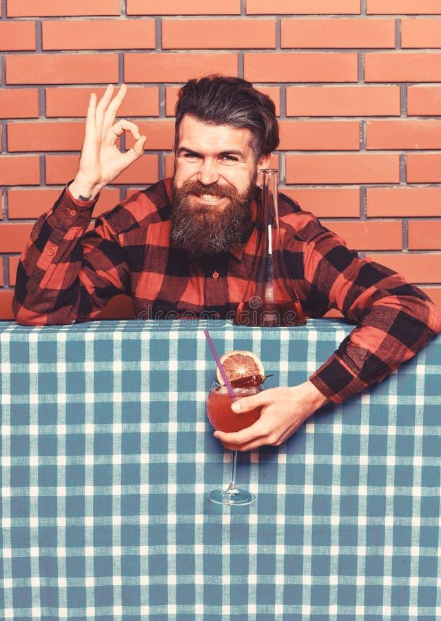 heerlijk concept Mens in geruit overhemd dichtbij fles, bakstenen muurachtergrond De barman met baard op vrolijk gezicht houdt royalty-vrije stock afbeeldingen