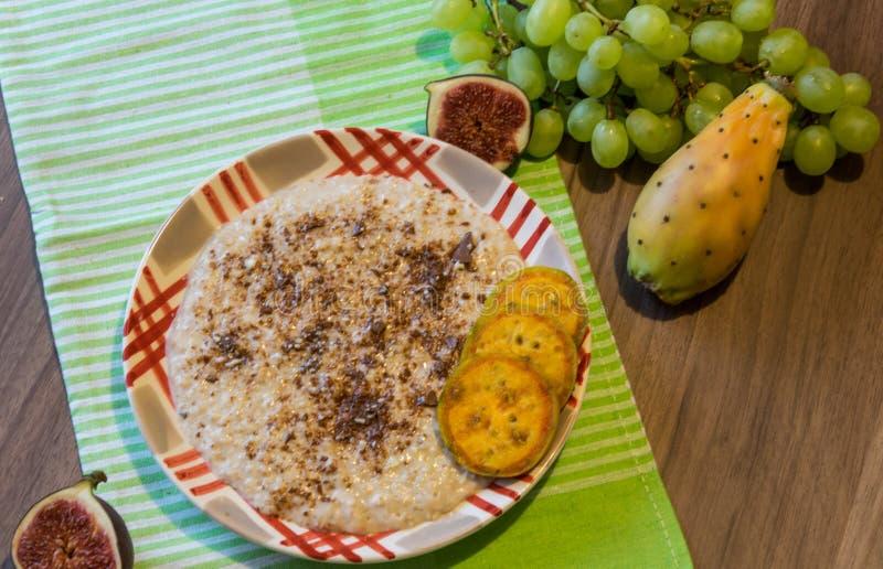 Heerlijk die havermeel met chocolade en stukken van fruit van fig., bananen, druiven en cactussenfig. wordt gemaakt stock fotografie