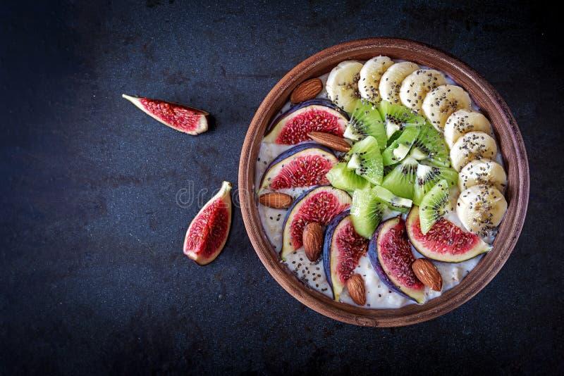 Heerlijk en gezond havermeel met fig., kiwi, banaan, amandel en chiazaden stock afbeeldingen