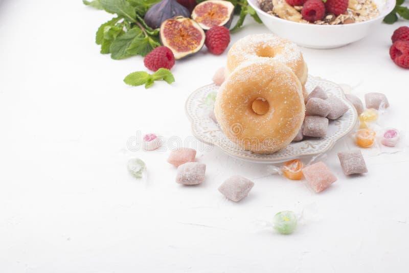 Heerlijk en gezond ontbijt op een witte achtergrond Vruchten, appelen, frambozen, fig., verse munt en donuts met suiker voor a royalty-vrije stock afbeeldingen