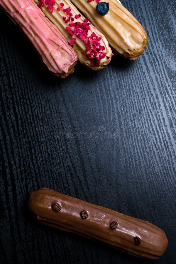 heerlijk gekleurd eclairs met koffiebonen en bosbes, framboos stock afbeeldingen