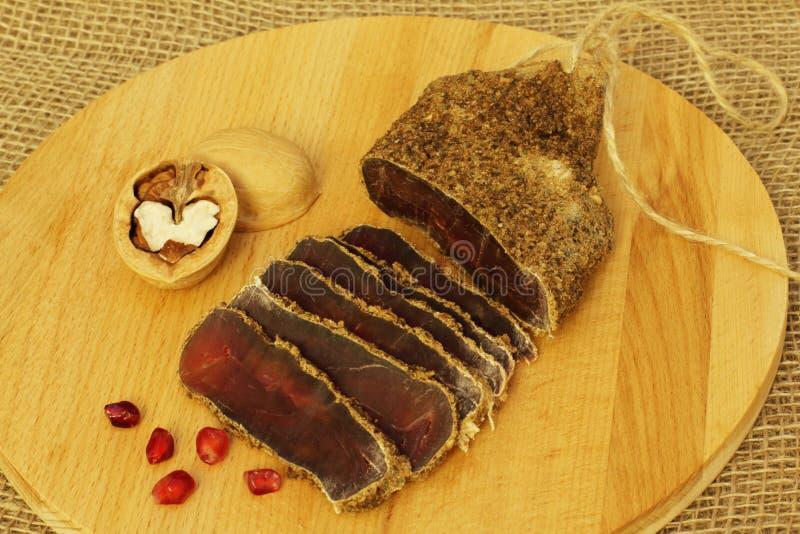 Heerlijk geurig smakelijk kruidig droog gezouten vlees met kruiden met rode granaatappelzaden en okkernoten op natuurlijke houten stock foto