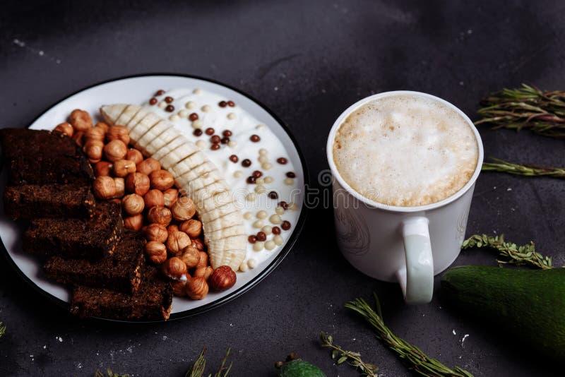 Heerlijk gezond Ontbijt in de ochtend Roggebrood, banaan, hazelnoot, chocolademuesli, yoghurt en en een Kop van koffie met stock fotografie