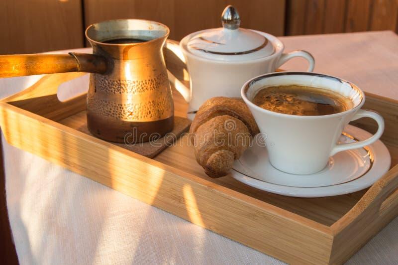 Heerlijk klassiek Ontbijt op een houten dienblad-uitstekend koper cezve, een Kop van koffie en een croissant, dageraadachtergrond royalty-vrije stock foto's