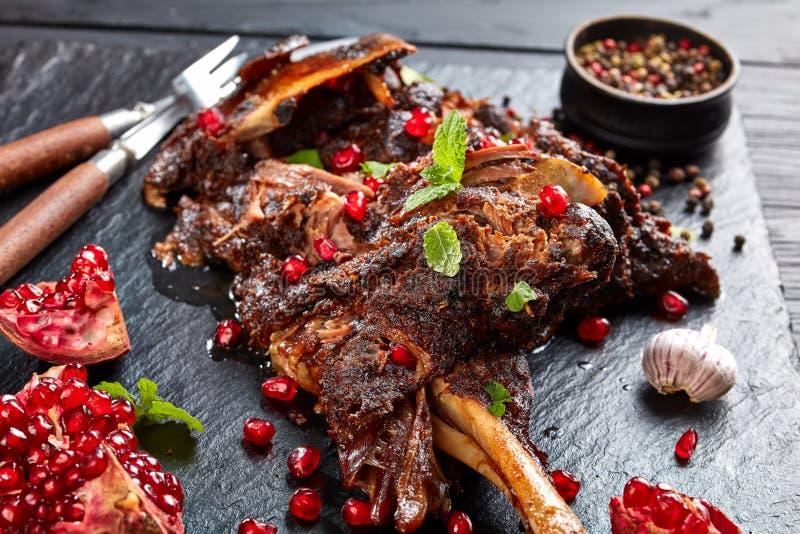 Heerlijk langzaam gekookt been van lam met granaatappelzaden, muntbladeren, kruiden en rozemarijn op een zwarte leiplaat op houte royalty-vrije stock foto