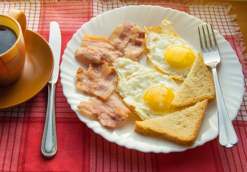 Heerlijk Ontbijt - een Kop van koffie, een plaat van gebraden eieren, bacon en toost, naast het Bestek op rood geruit servet stock foto's