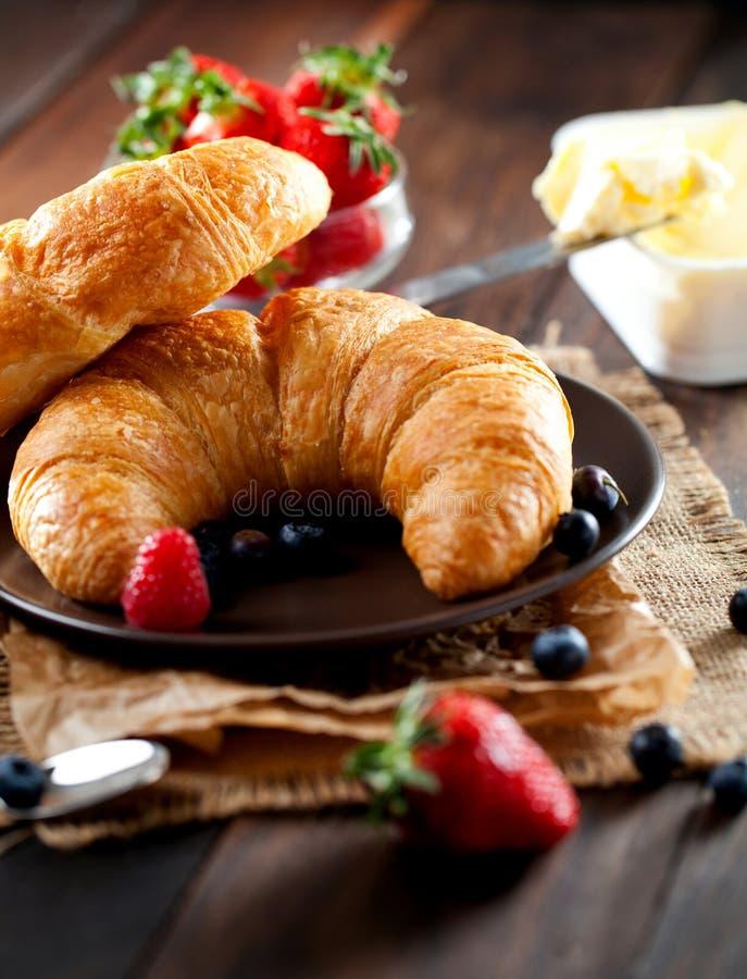 Heerlijk ontbijt met verse croissants en rijpe bessen op oude houten achtergrond royalty-vrije stock afbeeldingen