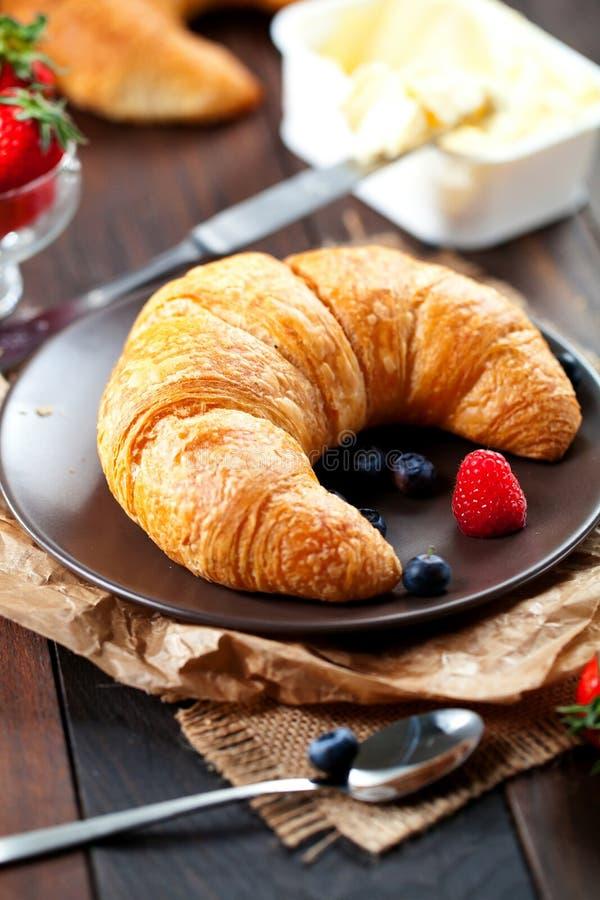 Heerlijk ontbijt met verse croissants en rijpe bessen op oude houten achtergrond stock afbeelding