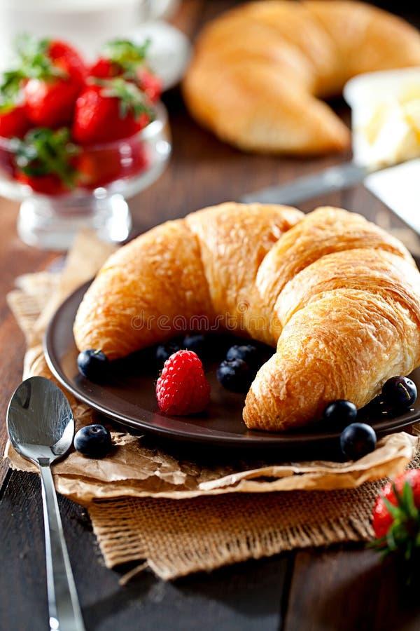 Heerlijk ontbijt met verse croissants en rijpe bessen op oude houten achtergrond stock foto's