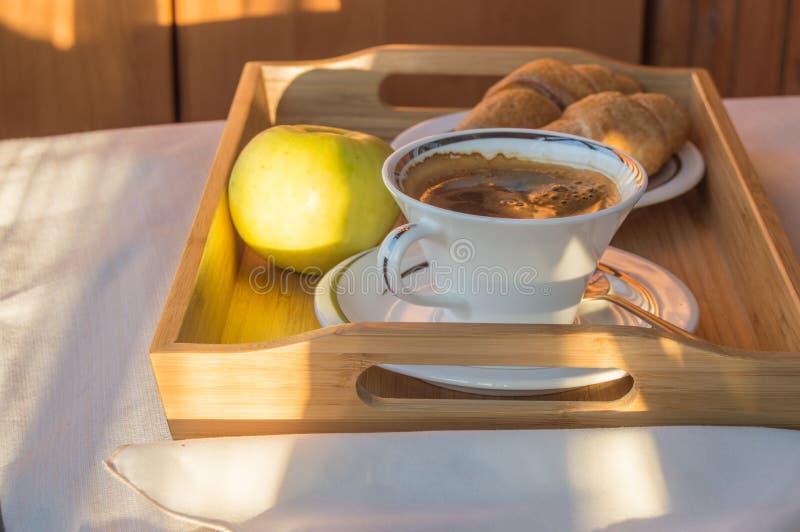Heerlijk Ontbijt op het balkon in het zonlicht, met koffie, croissants, Apple op een houten dienblad royalty-vrije stock foto