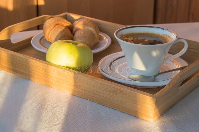 Heerlijk Ontbijt op het balkon in het zonlicht, met koffie, croissants, Apple op een houten dienblad stock foto's