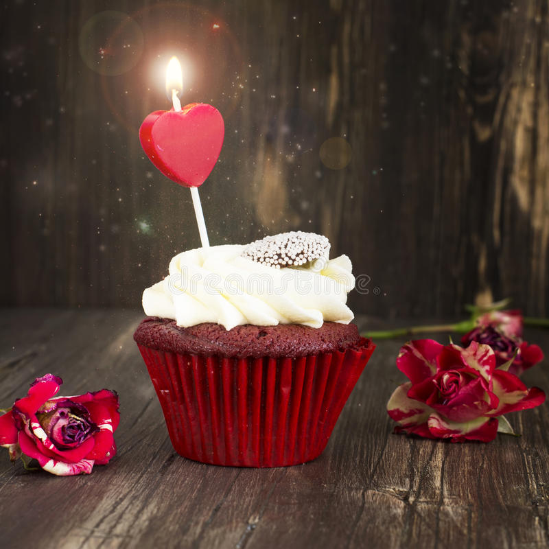 Heerlijk rood fluweel cupcake met het branden van kaars stock afbeeldingen