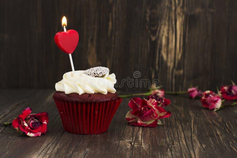 Heerlijk rood fluweel cupcake met het branden van kaars stock foto