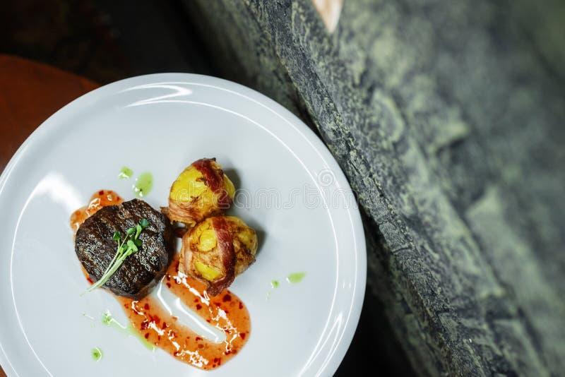 Heerlijk sappig rundvleeslapje vlees met een broodje van gebraden bacon met saus op een plaat in een uitstekend restaurant Gastro royalty-vrije stock afbeeldingen