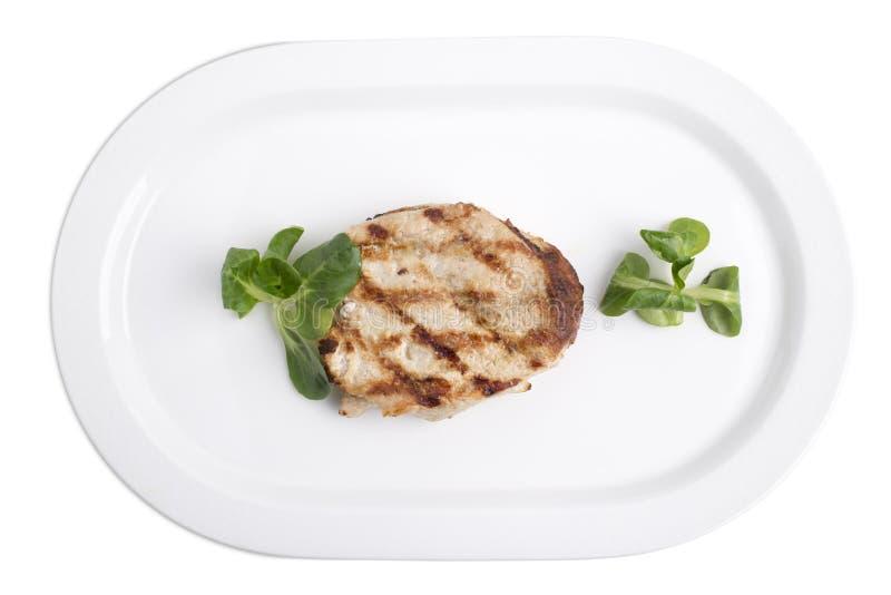 Heerlijk varkensvleeslapje vlees in een witte plaat stock fotografie