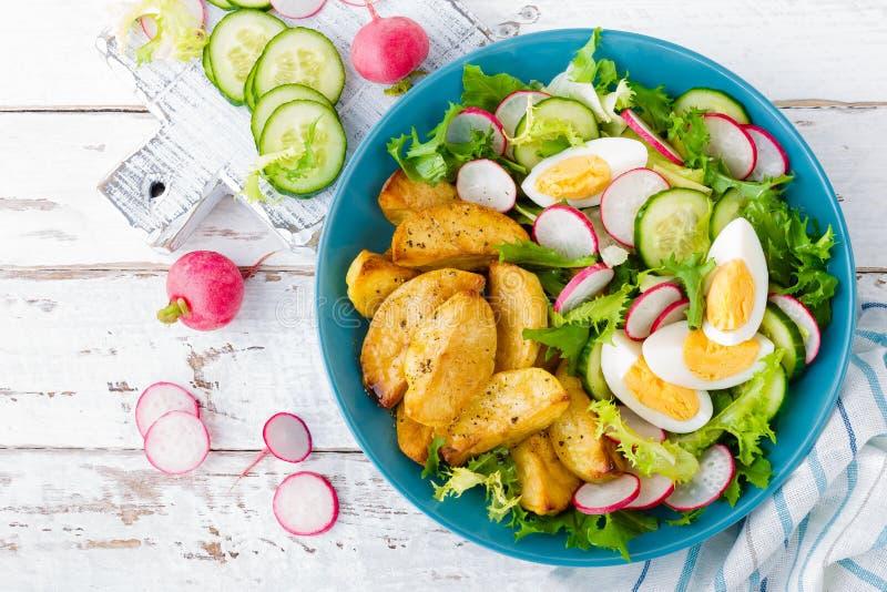 Heerlijke aardappel in de schil, gekookt ei en verse groentesalade van sla, komkommer en radijs De zomermenu voor detoxdieet stock afbeelding