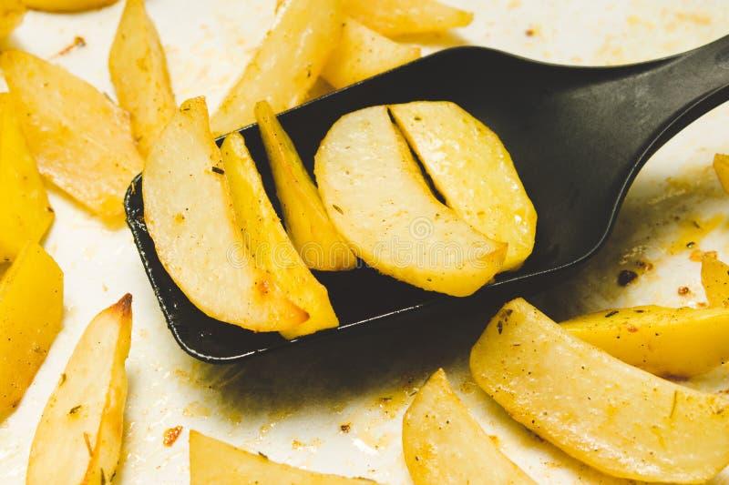 Heerlijke aardappelen in de schil met rozemarijn op perkament op zwarte plastic lepel Vegetarisch voedsel De stijl van het aardap stock afbeelding