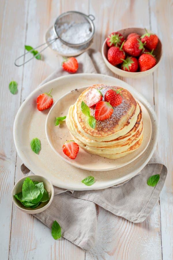 Heerlijke Amerikaanse pannekoeken met verse zoete aardbeien en suiker stock afbeelding