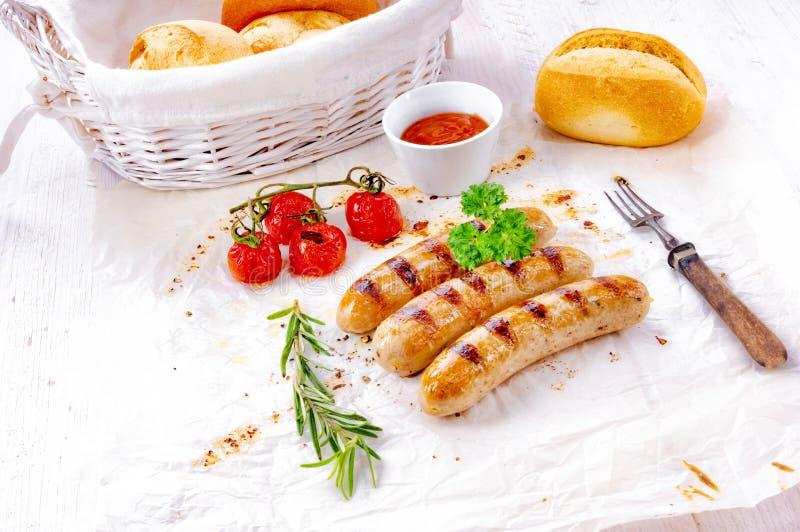 Heerlijke braadworst met ketchup en verse broodjes royalty-vrije stock foto