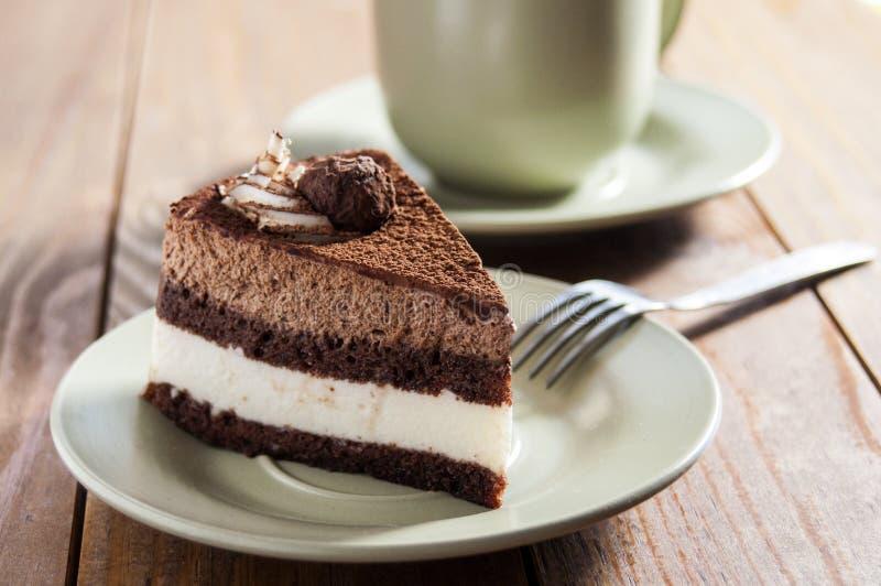 Heerlijke cake Lagen van gevoelig room en chocoladebiscuitgebak Voor een plaat, dichtbij vork en kop Op een donkere houten achter royalty-vrije stock afbeeldingen