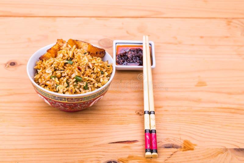 Heerlijke Chinese kruidige gebraden rijst met braadstukvarkensvlees in kom stock afbeelding