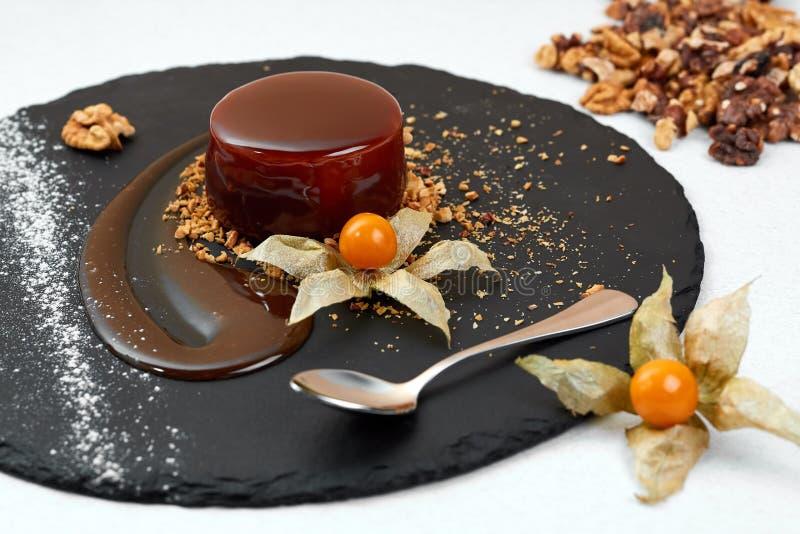 Heerlijke Chocolade verglaasde cirkelcake op zwarte schalie Chocoladedessert met Okkernoot Restaurant Gestileerde samenstelling royalty-vrije stock foto