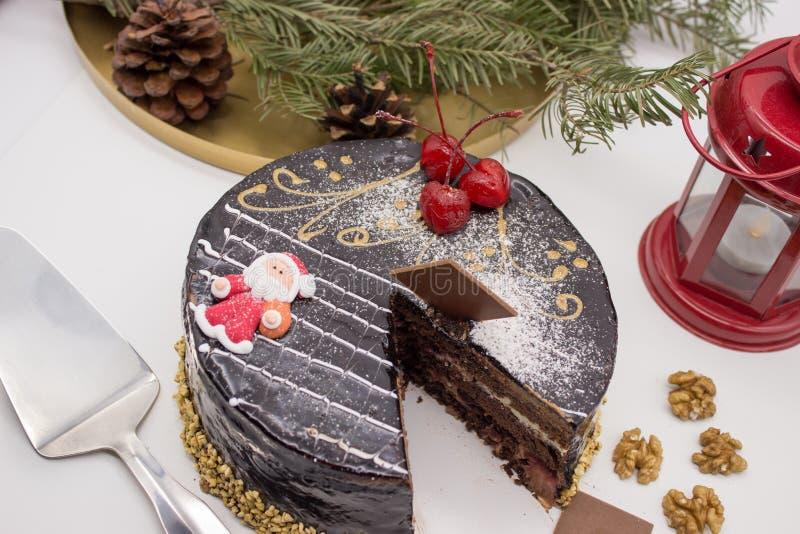 Heerlijke chocoladecake, verfraaide kersen, en suikerkerstman en knapperige noten, met Kerstmisdecor en ornamenten stock foto