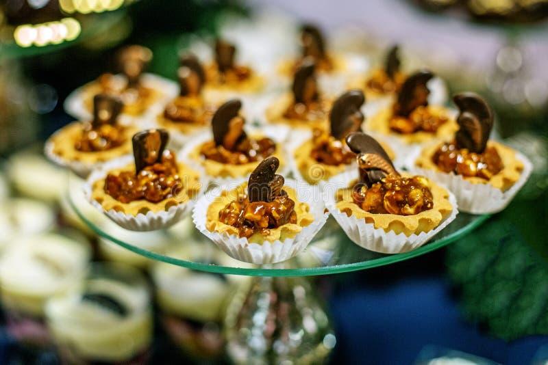Heerlijke chocoladeokkernoten op een glasdienblad Conceptenvoedsel, desse stock foto