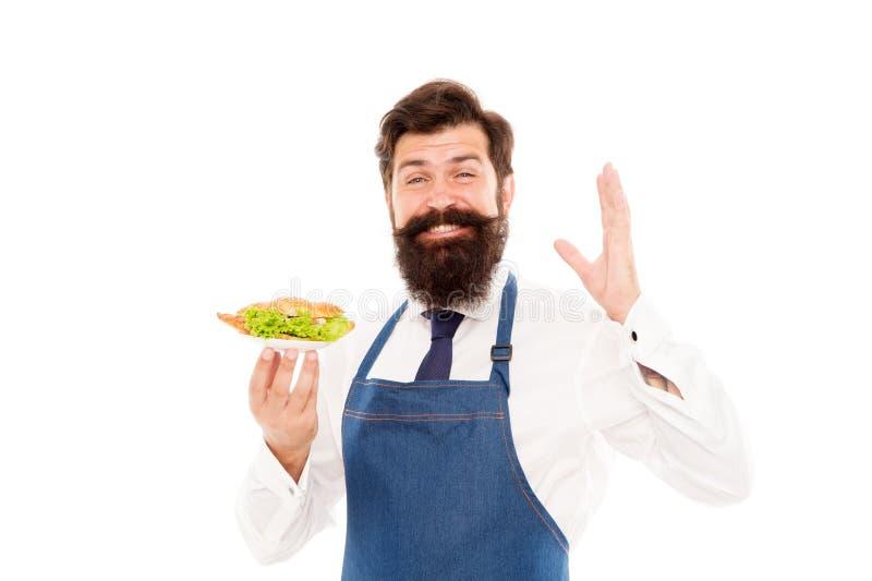 Heerlijke Croissant De slijtageschort van de mensen draagt de gebaarde kelner plaat met schotel Koffieconcept Gevuld kerel dienen stock afbeelding