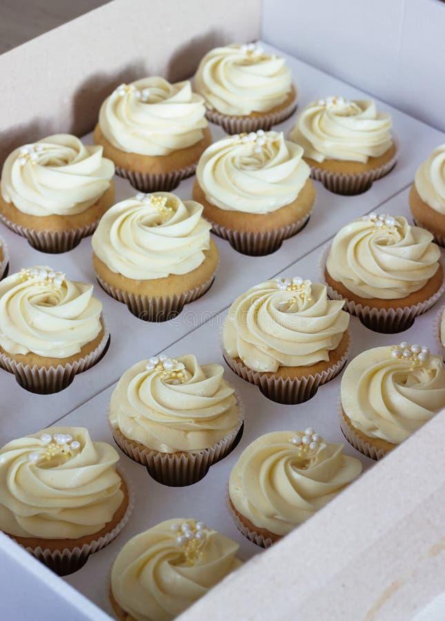 Heerlijke cupcakes in kartondoos met een hoed in de vorm van namen toe stock afbeeldingen