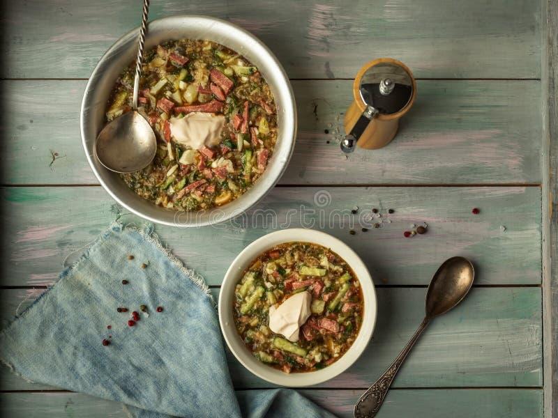 Heerlijke de zomersoep op kwas met verse groenten en worst in twee verschillende platen met soeplepels en een servet op houten stock foto's