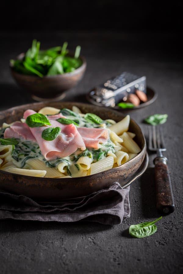 Heerlijke deegwaren met bechamelsaus, ham en spinazie royalty-vrije stock afbeeldingen